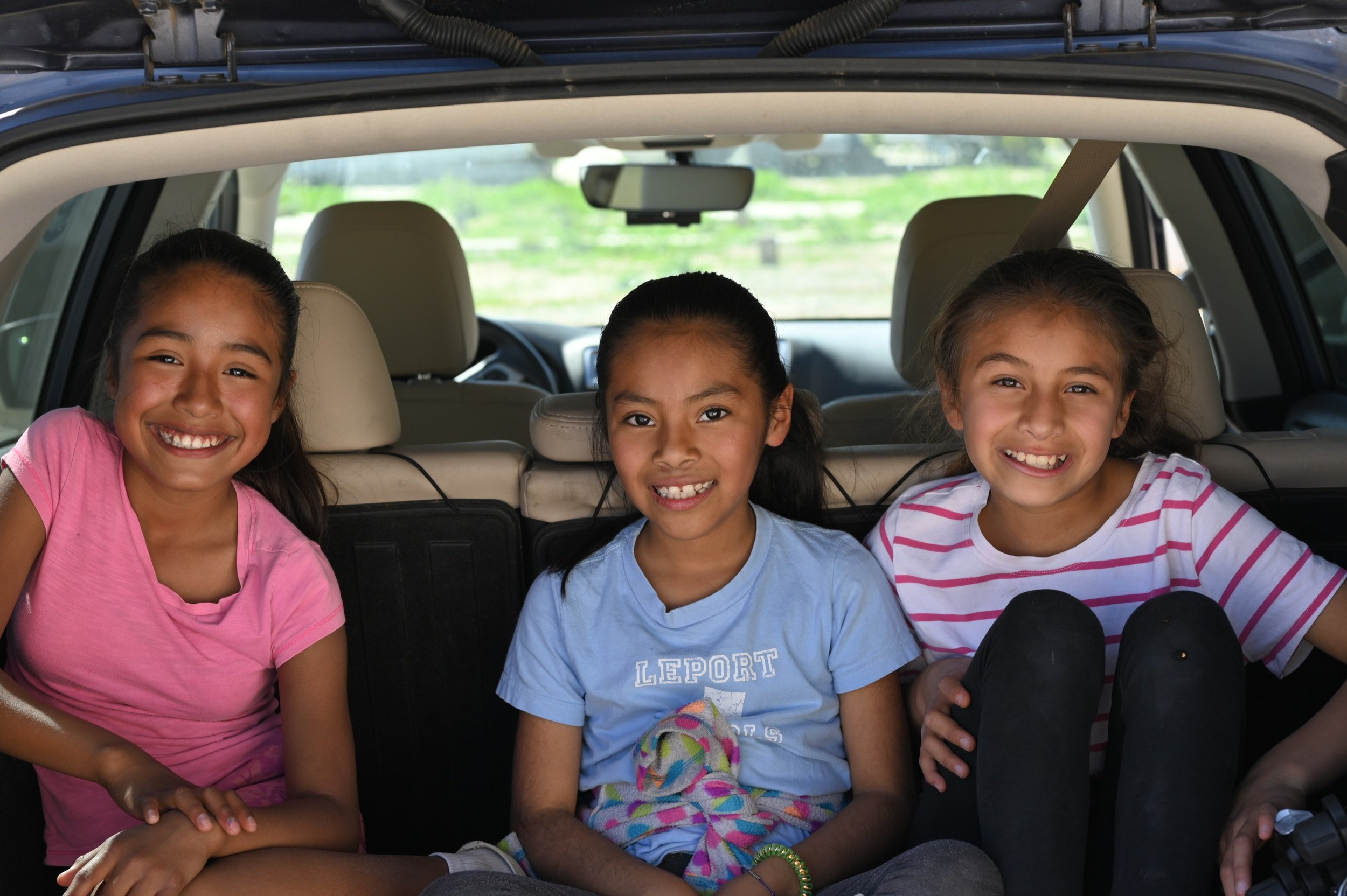 Children smiling and sitting in the back seat of the car