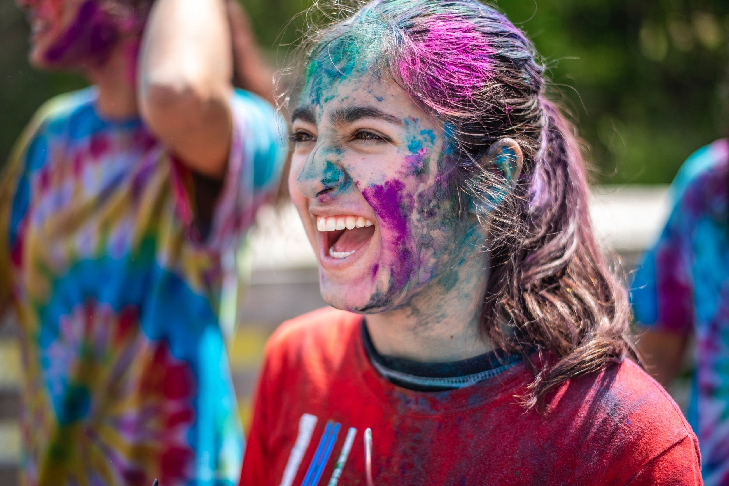 fille couverte de peinture, sourire large