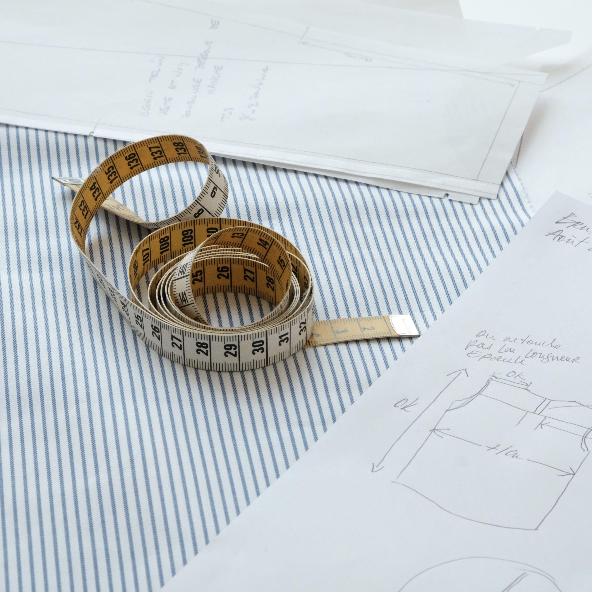 mètre de couture sur croquis, main et crayon