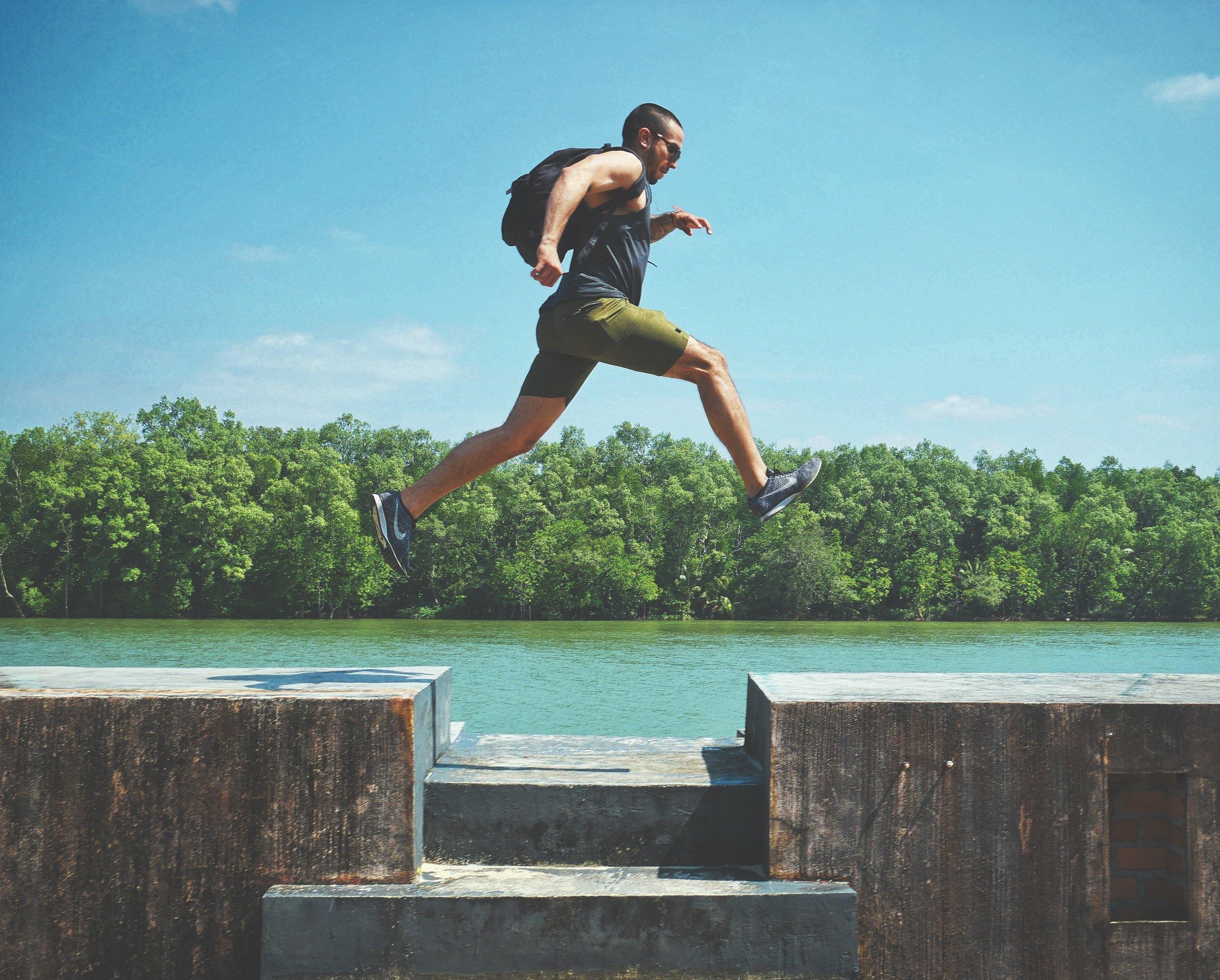 homme en sac à dos sautant au dessus d'un trou, derrière eau et forêt
