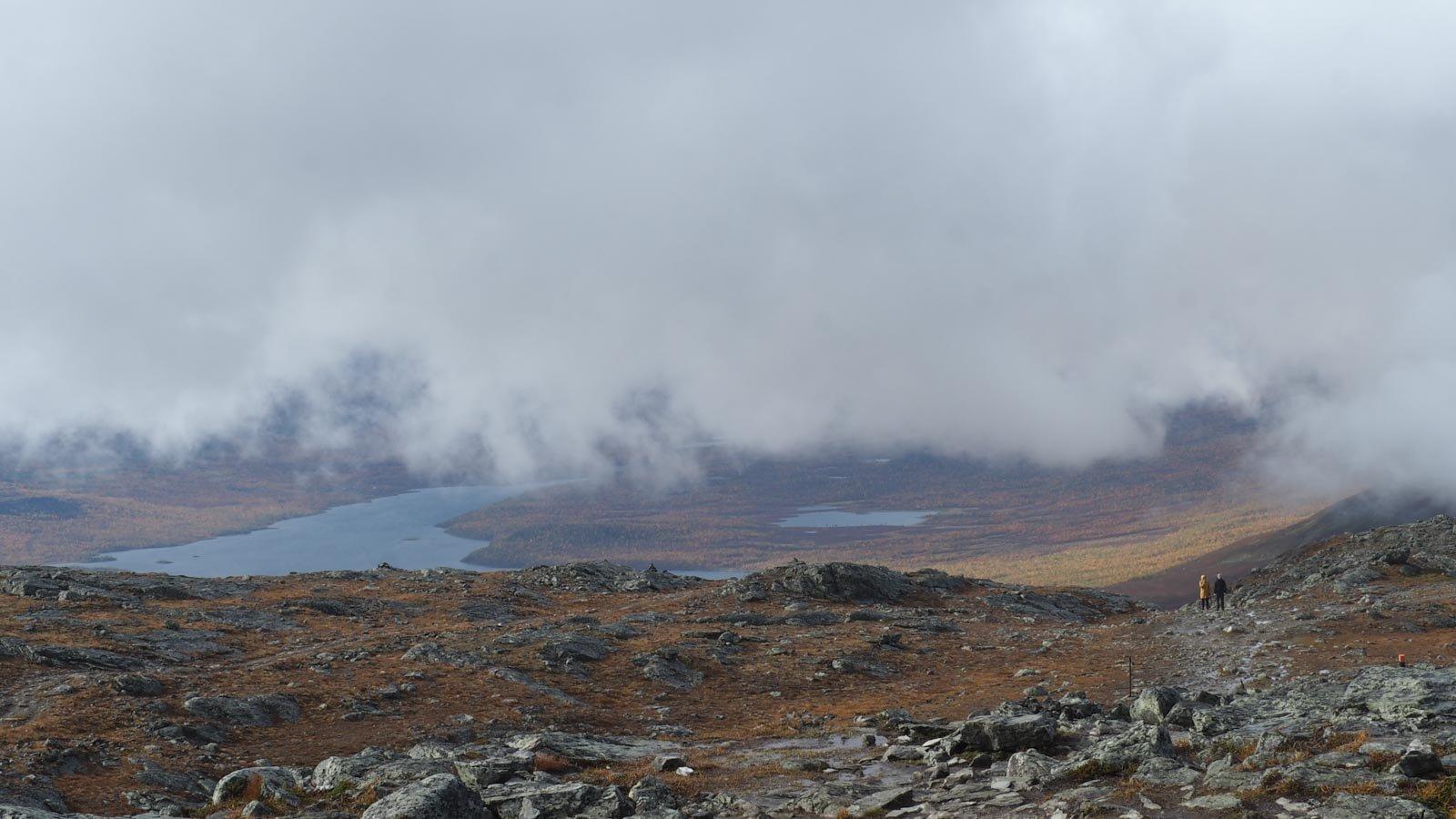 Näkymä Saanatunturin laelta: etualalla näkyy kivistä tunturin lakea, mutta matalalla roikkuvat pilvet peittävät näkymän laaksoon.