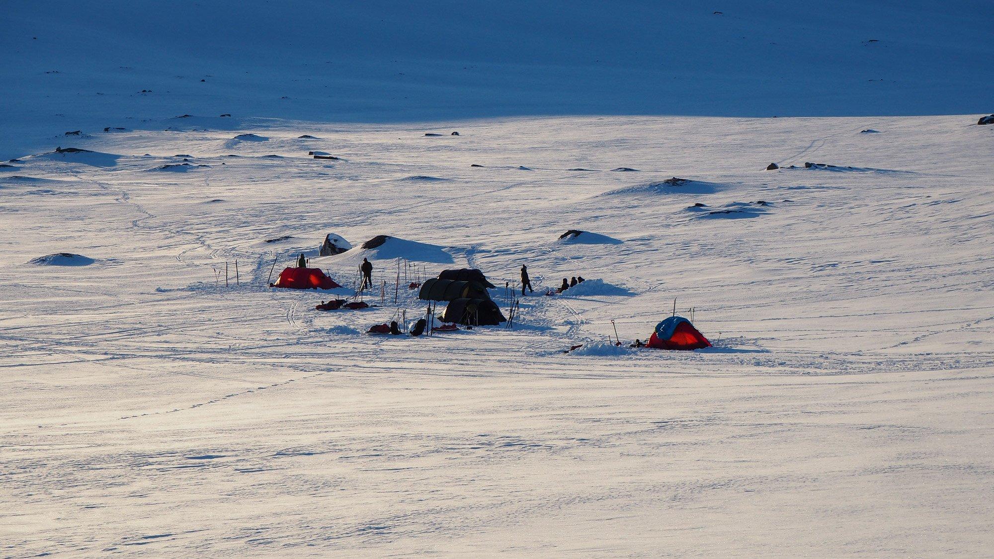 Kuvassa 5 teltan leiri lumisessa laaksossa.