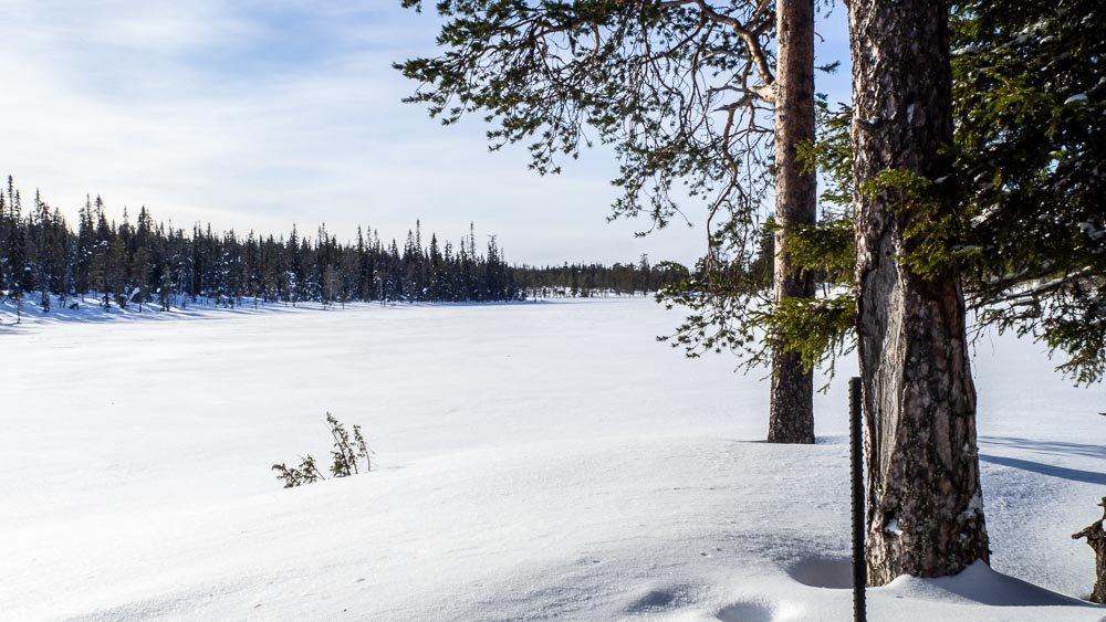 Lumen peittämä erämaajärven selkä hohtavassa auringonpaisteessa.