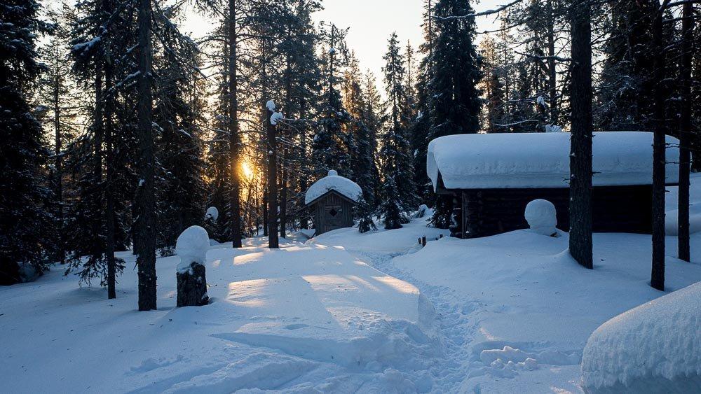 Aikainen aamu Riisitunturin erämaassa. Aurinko on nousemassa puiden takana. Kuvassa lumen peittämä hyyskä ja liiteri.