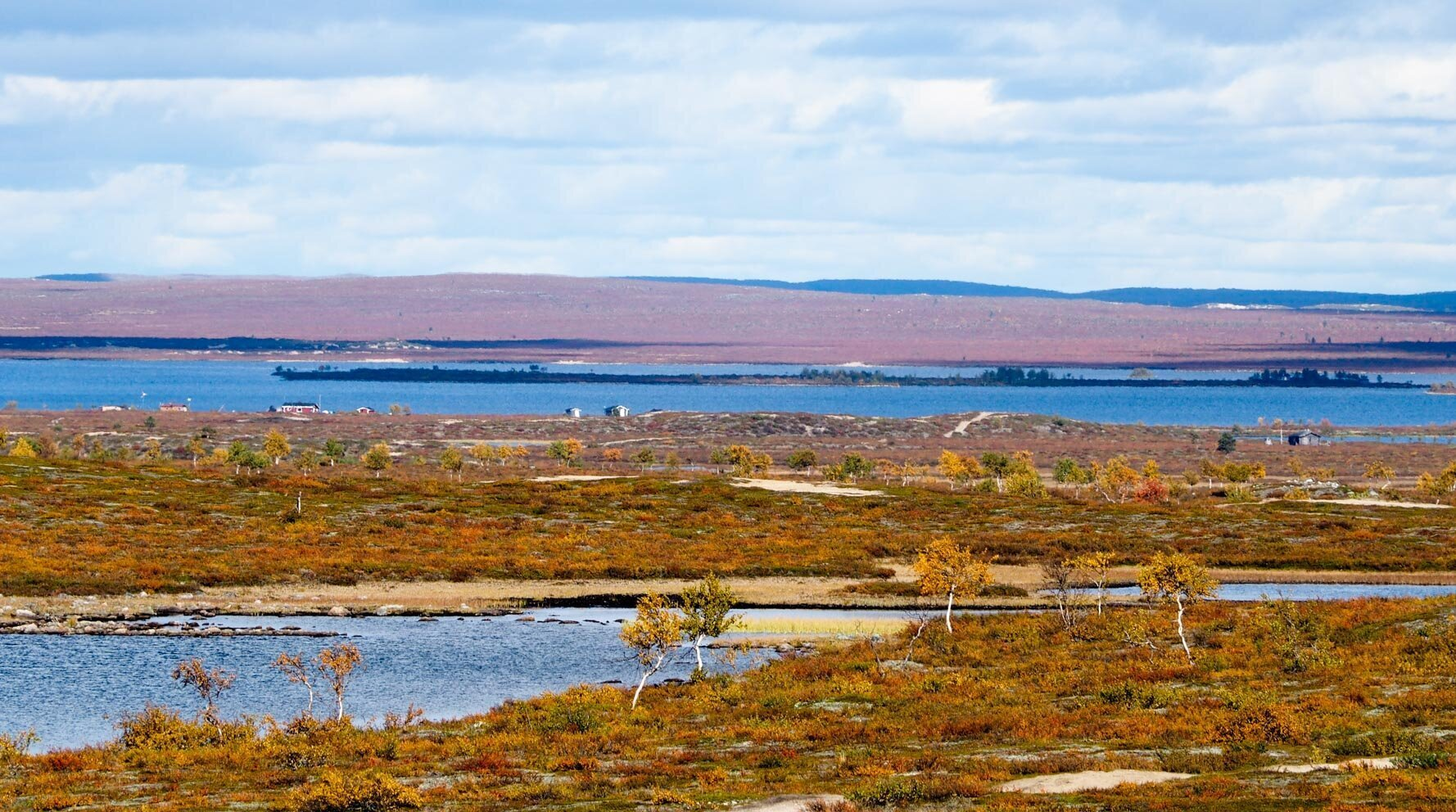 Kuvassa etualalla ruskan värjäämää varvikkoa ja kauempana siintää sininen järvi. Järven rannalla muutama pieni kesämökki.