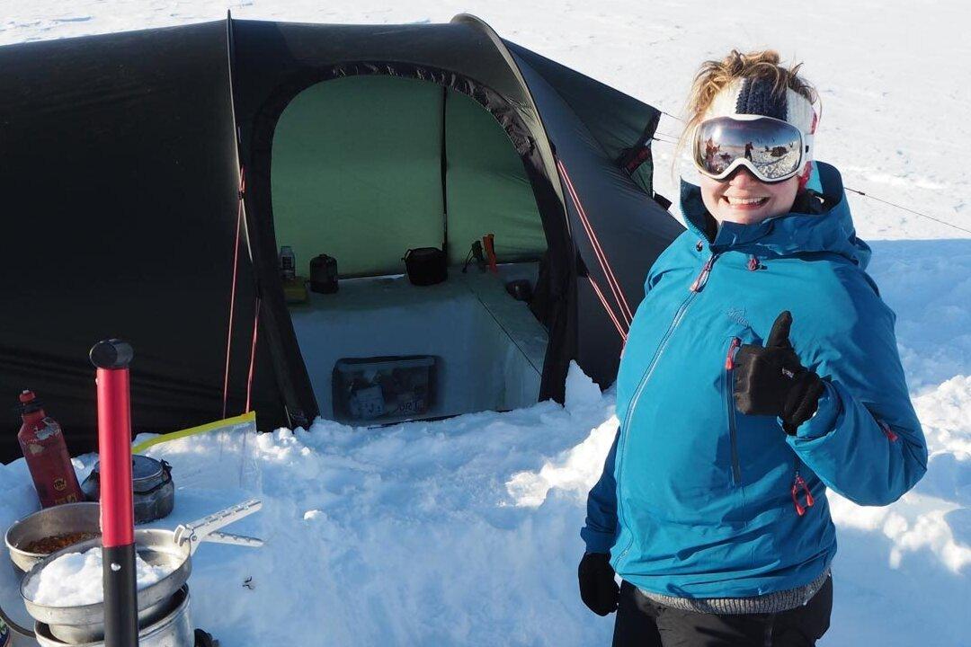 Lumihangessa seisova nuori nainen hymyilee ja näyttää peukkua. Naamallaan hänellä on heijastavat laskettelulasit.