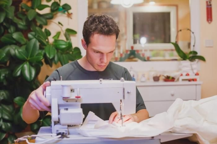 man sewing in his home