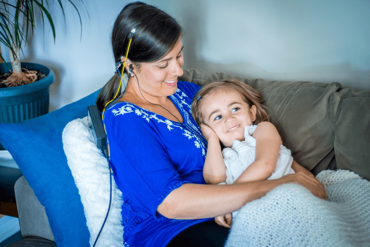 Photo of women having a neurofeedback session while holding a little girl and both are smiling.