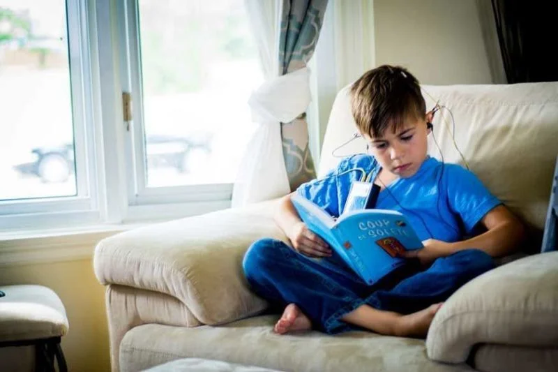 Photo of a little boy ready a book during a neurofeedback session.