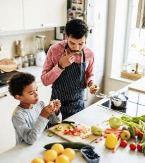 African American father and young son cooking together in kitchen