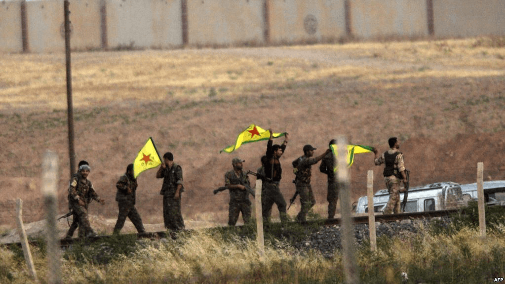 مقاتلون من وحدات حماية الشعب الكردية قرب معبر أكاكالي على الحدود بين سورية وتركيا منتصف العام 2015