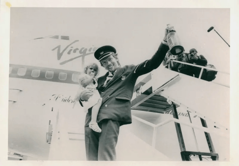 Richard holding his daughter Holly as he celebrates launching Virgin Atlantic