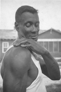 An African American man with his hand on one shoulder.