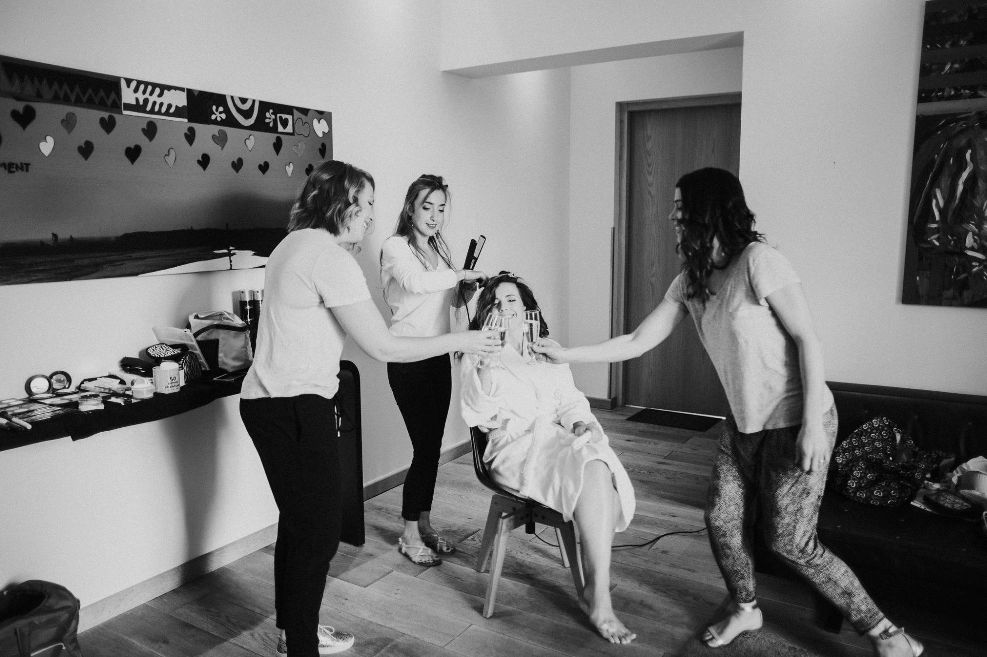Mariée qui se fait coifer par Anais Faure en buvant du champagne avec ses demoiselles d'honneur