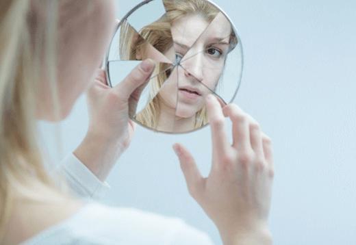 A woman looking in a broken mirror.