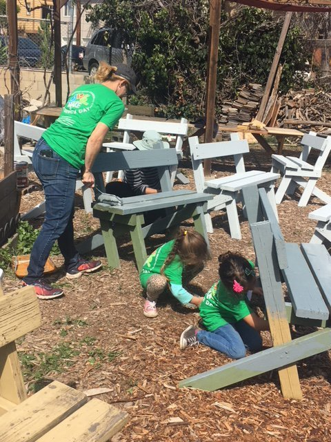 Rebecca Ochoa painting benches with daughters Isabella and Grace