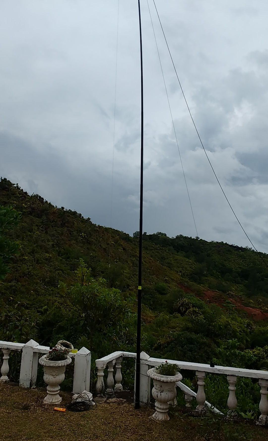 Picture showing his setup in Praslin telescopic mast and OCF antenna covering 80m band