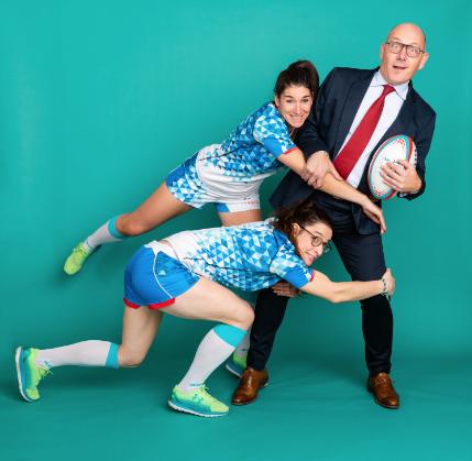 Alexandra et Laura en tenues de rugbywoman faisant un plaquage, tout en sourires, à Jannick, en costard cravate, qui ne sait pas trop quoi faire du ballon. Fond vert turquoise.