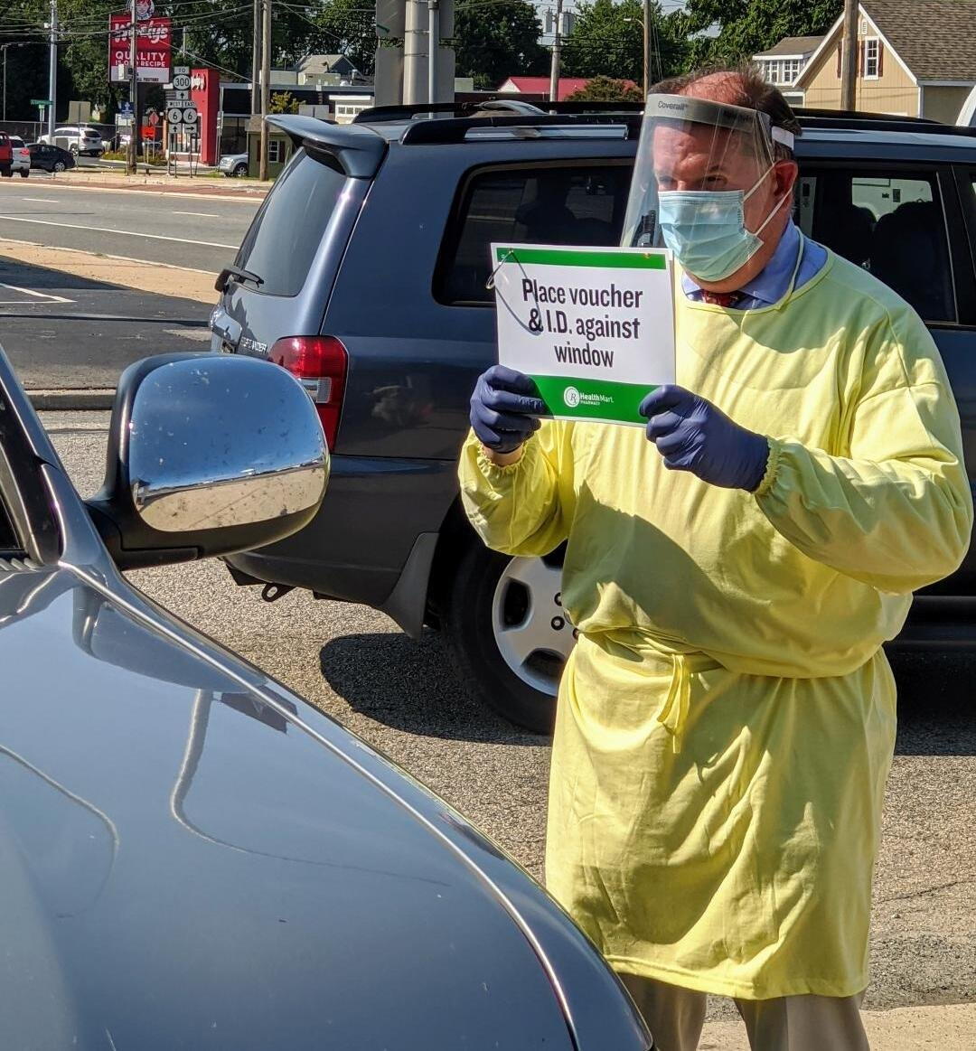 Kevin in the parking lot with a sign for a patient taking a COVID19 test
